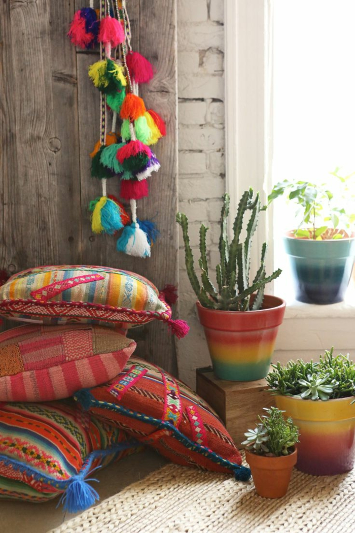 deco boheme, murs en bois et briques, grande fenêtre, coussins multicolore