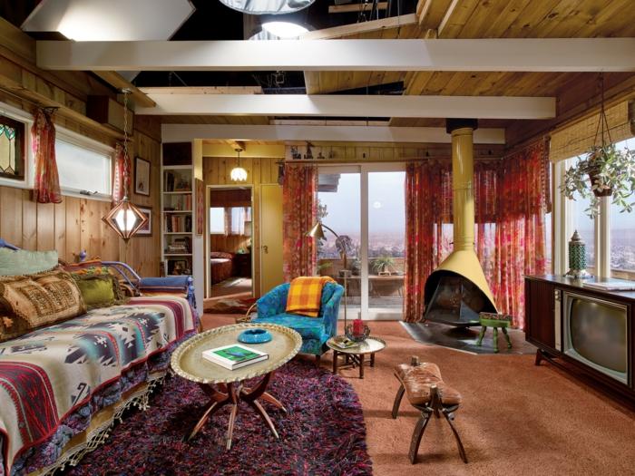 chambre hippie, murs en bois, tapis ethnique, cheminée moderne, fauteuil bleu foncé, grande fenêtre