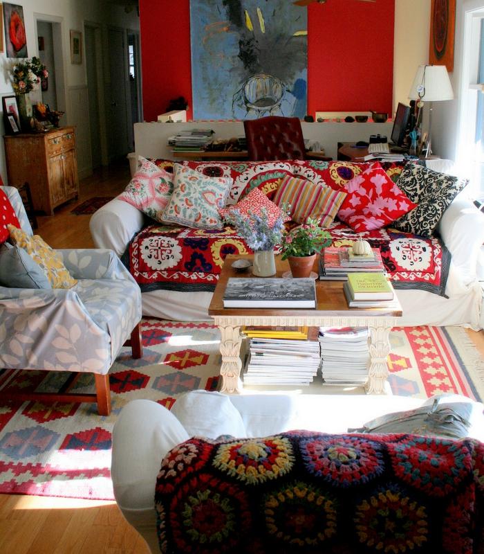 chambre hippie, parquet en bois, mur rouge, coussins à motifs ethniques