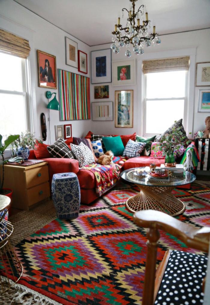 chambre hippie, murs blancs, lustre en cristaux, grandes fenêtres, table ronde, canapé rouge