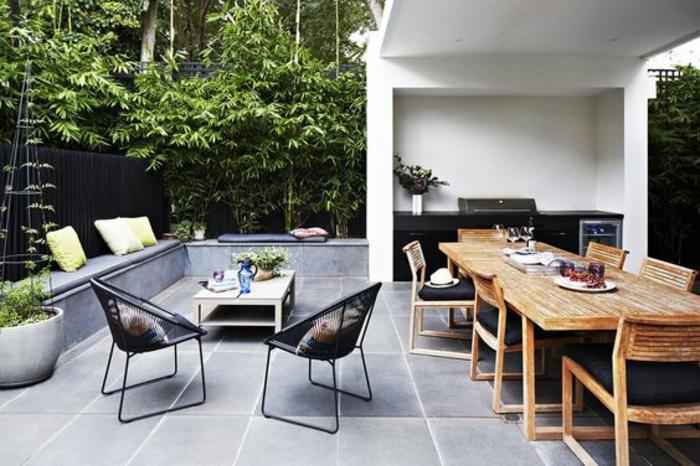 une élégante cuisine d'été couverte en noir, terrasse accueillante d'un aménagement fonctionnelle