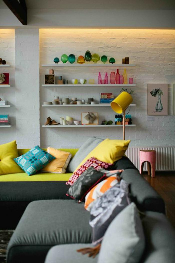 salon gris et jaune, lampe jaune, étagère blanche, mur en briques blanches