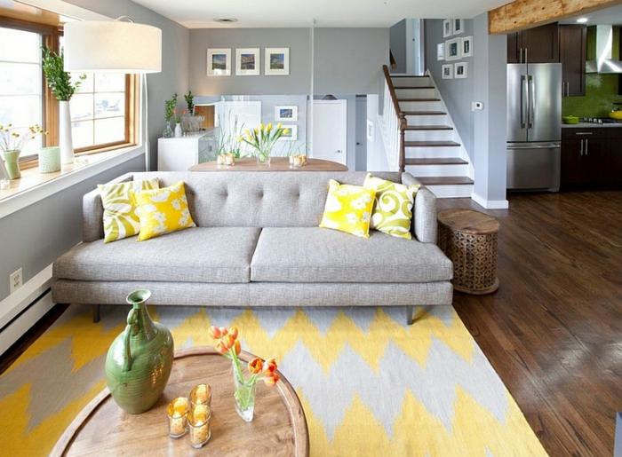 salon gris et jaune, tapis gris et table ovale en bois, coussins jaunes sur un grand sofa gris
