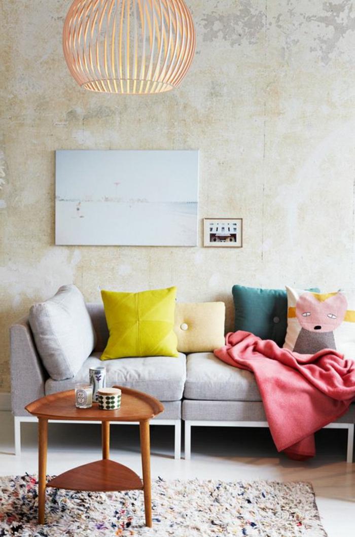 salon gris et jaune, coussins déco et sofa gris, table basse en bois, mur effet béton