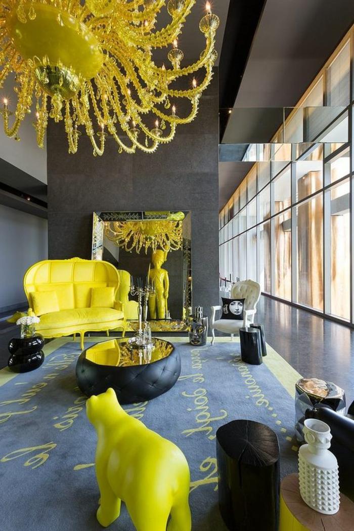salon gris jaune, plafonnier extravagant, sofa jaune et statuette oursn tapis bleu
