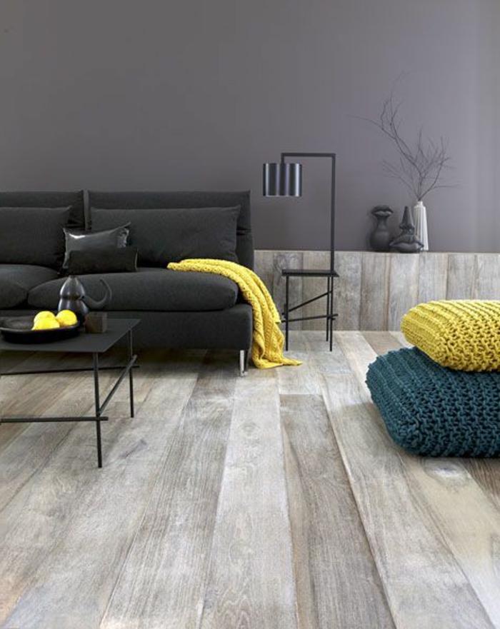 salon jaune et gris, coussins de sol tricotés, canapé gris sombre, sol en bois