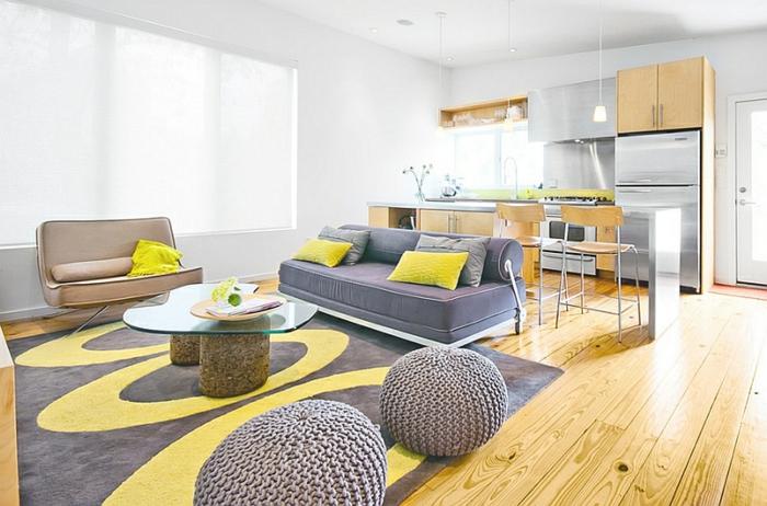 salon jaune et gris, tapis bicolore en jaune et grisn poufs tricotés, cuisine à plan ouvert