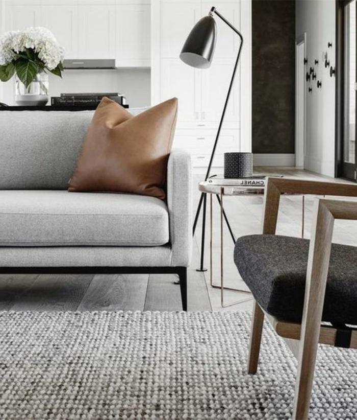 salon minimaliste, sofa gris scandinave et coussin en cuir, lampe se dol noire