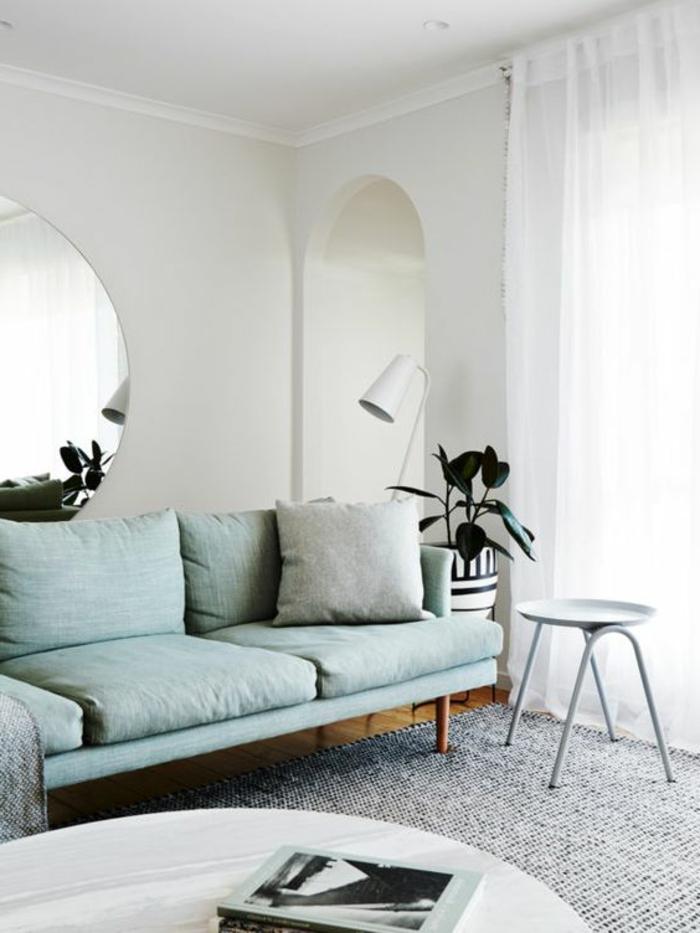 salon minimaliste, miroir mural rons, sofa bleu et coussins bleus