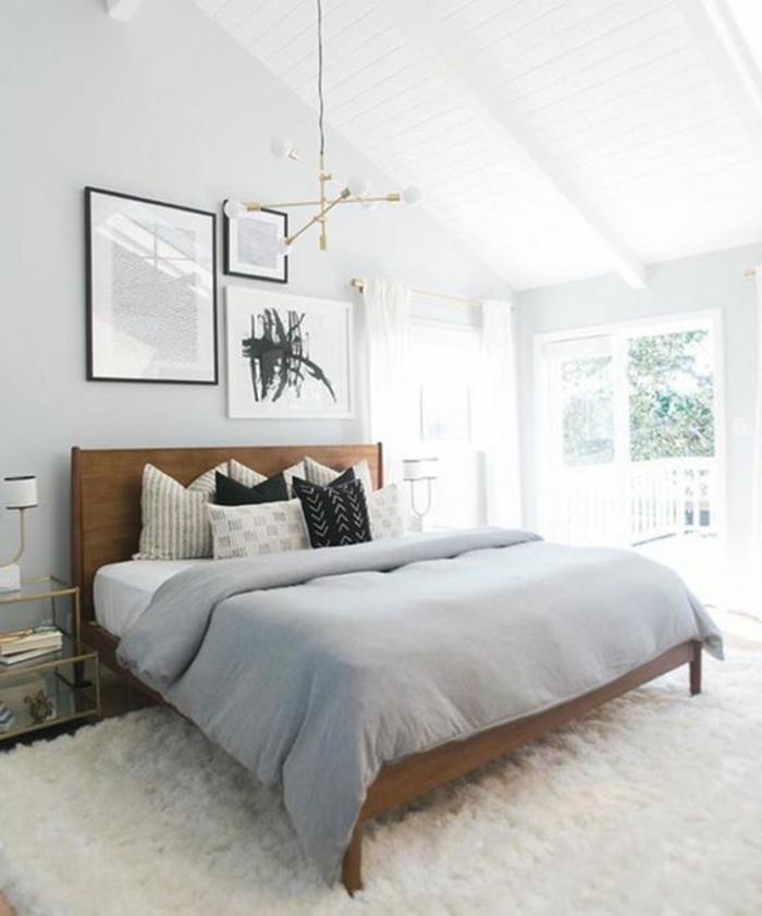 tapis blanc, lit en bois, couverture de lit grise, coussins en blanc, gris et noir, couleur mur blanc, suspension design, tableaux decoratifs