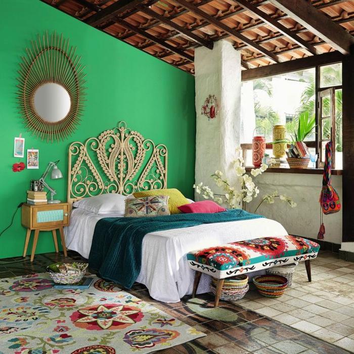 chambre hippie, miroir ovale, grande fenêtre, mur vert, plafond avec poutres en bois, panier en paille