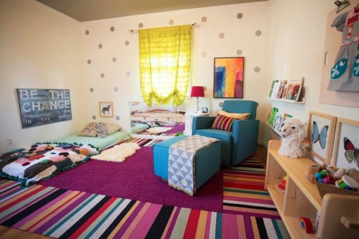 mur couleur blanche, points gris, etageres rangement livres, tapis multicolores, fauteuil blei, lit bébé montessori au sol, style bohème, jouets, décorations