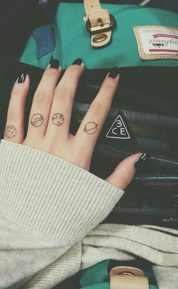 un tatouage sur les doigts à motif planètes, tatouage à la fois simple et original