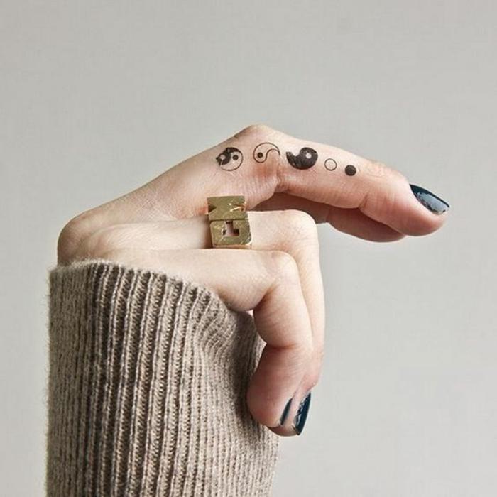 un tatouage main traditionnel représentant le yin et le yang