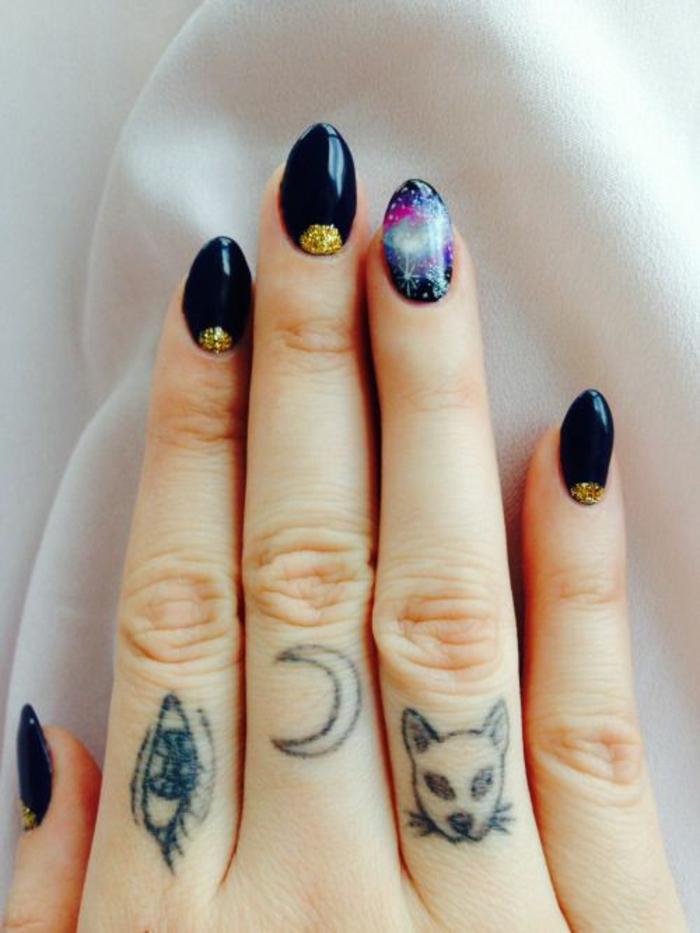 un joli nail art galaxie et un tatouage sur les doigts chargé de symbolisme