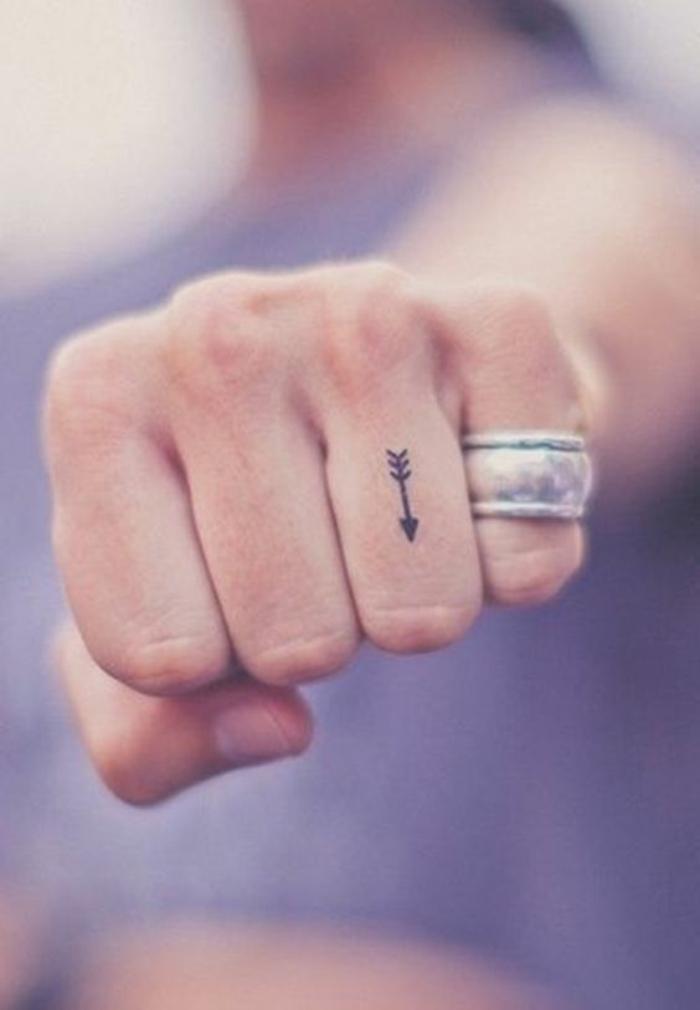 jolie petite flèche tatouée sur le doigt, tatouage sur le doigt discret et subtil