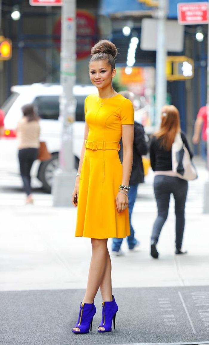 tenue chic robe jaune avec ceinture et des bottines en bleu royal avec un gros chignon