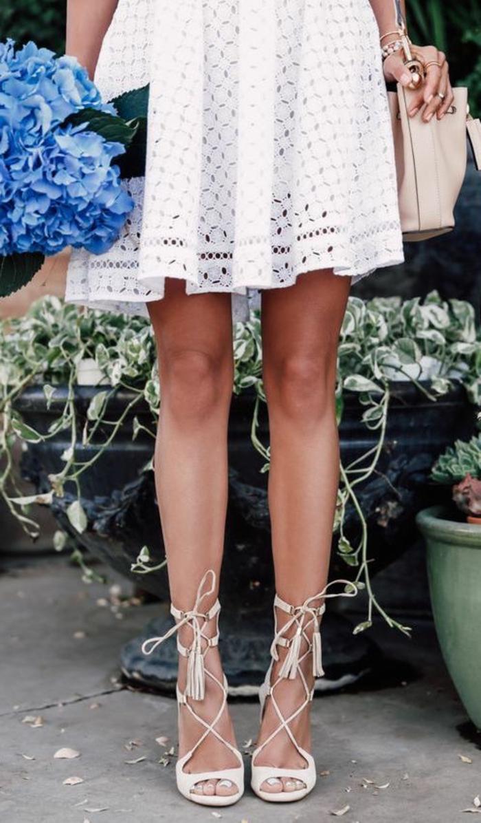 tenue chic détail choc robe en dentelle blanche mini avec sandales sexy et sac rose pastel