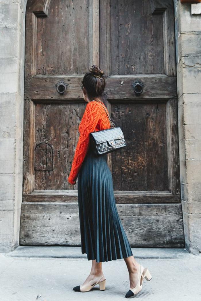 tenue chic et choc pull orange et jupe en bleu pétrole plissée avec des chaussures en beige et noir