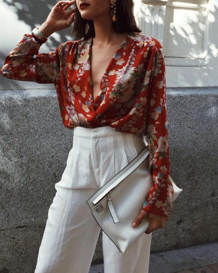 tenue chic femme en pantalon blanc et blouse grand décolleté grandes fleurs et sac pochette blanc