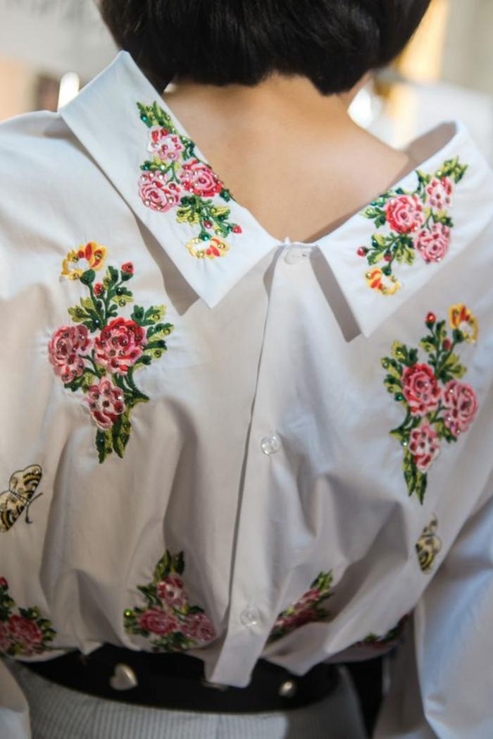 tenue chic blouse blanche au col claudine avec des fleurs brodés et ceinture noire à coeurs métalliques