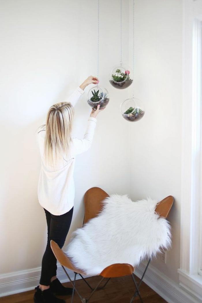 terrarium plante, plaid en fausse fourrure, parquet en bois, gilet blanc, fille blonde, terrarium suspendu