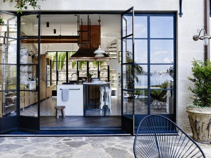 une cuisine d'été couverte de style industriel qui s'ouvre sur le jardin