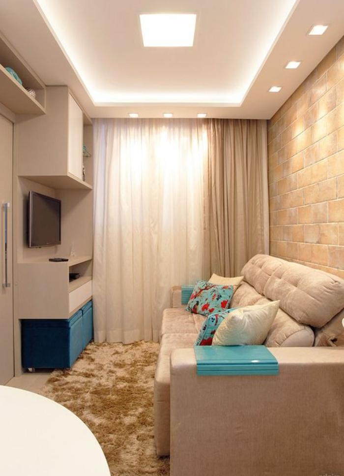 aménager une petite chambre, parement mural en pierre, tapis beige, grand sofa moelleux et tv suspendu