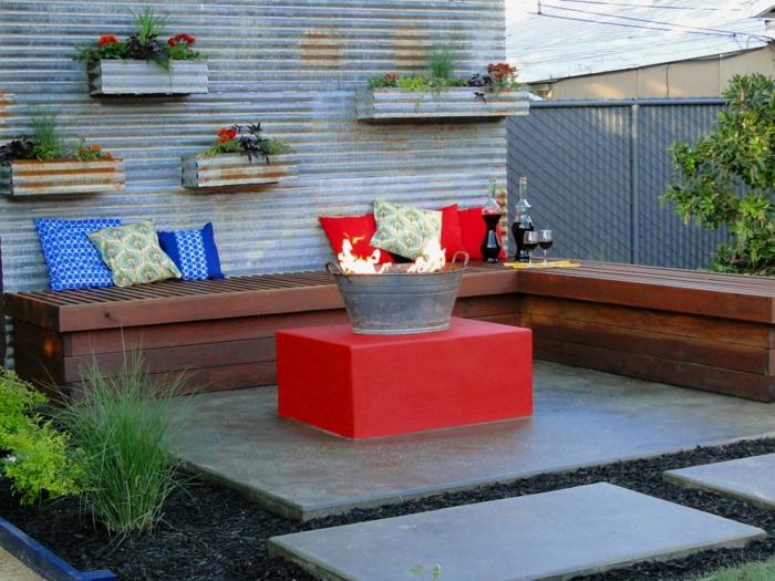 idee jardin, banc en palettes de bois, étagères florales, coussins bleu, coussins rouges, table rouge de jardin