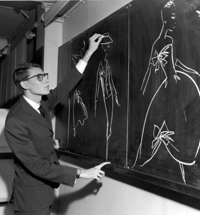 année 60, Yves Saint Laurent dessinant ses modèles sur un tableau noir