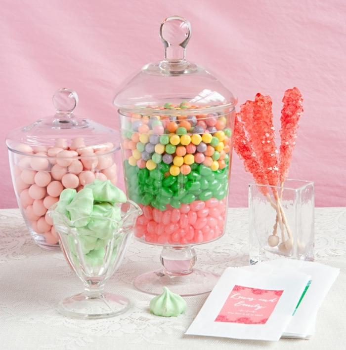 idée comment organiser un bar à bonbons, couleurs pastel, dragées colorées, sucettes, meringues verts, fond rose, nappe blanche, bonbonnière en verre