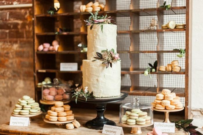 decoration bar a bonbon rustique chic, gateau de mariage à deux étages, décoration florale macarons rangées dans des présentoirs gateaux, fond meuble en bois vinatge, table rustique