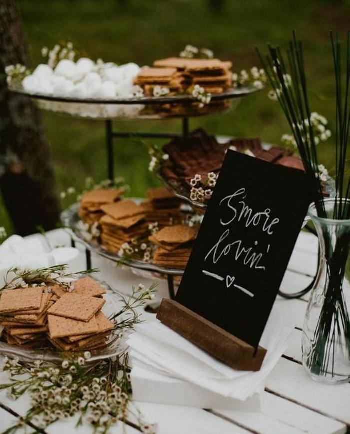 bar à bonbons mariage avec biscuits, fleurs, herbes fraiches, tableau noire décoratif, table blanche, guimauves, idee deco mariage en plein air