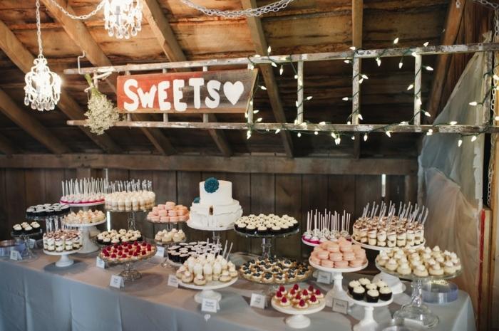 candy bar mariage, desserts, amcarons, tartalettes, cupcakes sur présentoir gateau de mariage, lustre elegantes, guirlande lumineuse et fond de décor rustique