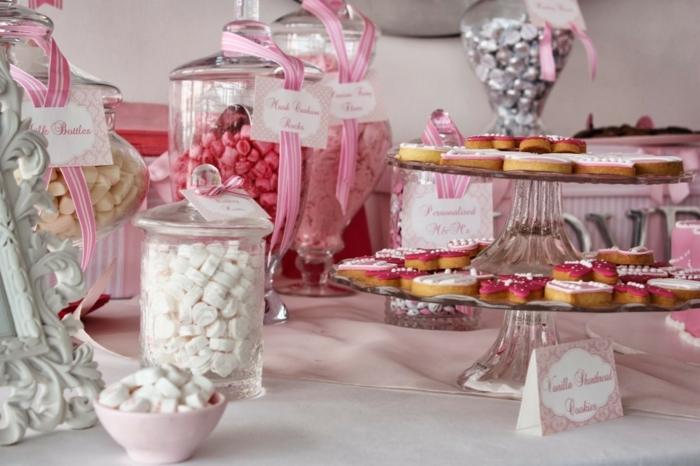 pastilles, réglisses et bonbons de sucre dans des bonbonnières en verre de taille différente, sablés sur des présentoirs gateau, rubans rose, bar à bonbons mariage
