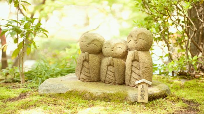 statue bouddha exterieur, idee deco jardin, plantes vertes, broussailles, mousse
