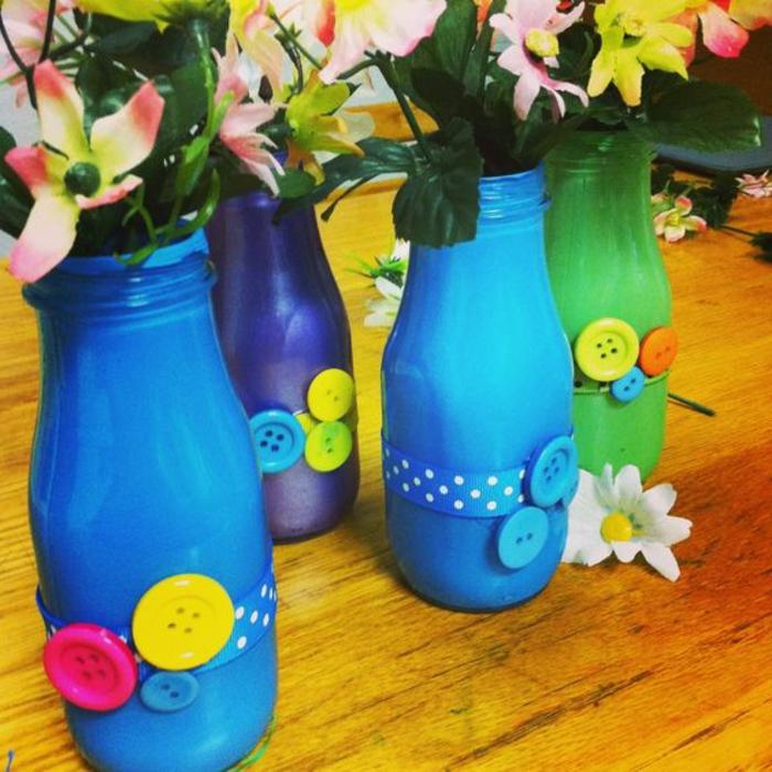 bouteilles en verre repeintes de couleurs diverses et customisés avec des boutons multicolores, vase de fleurs avec des bouquets de fleurs, cadeau pour la fête des mères