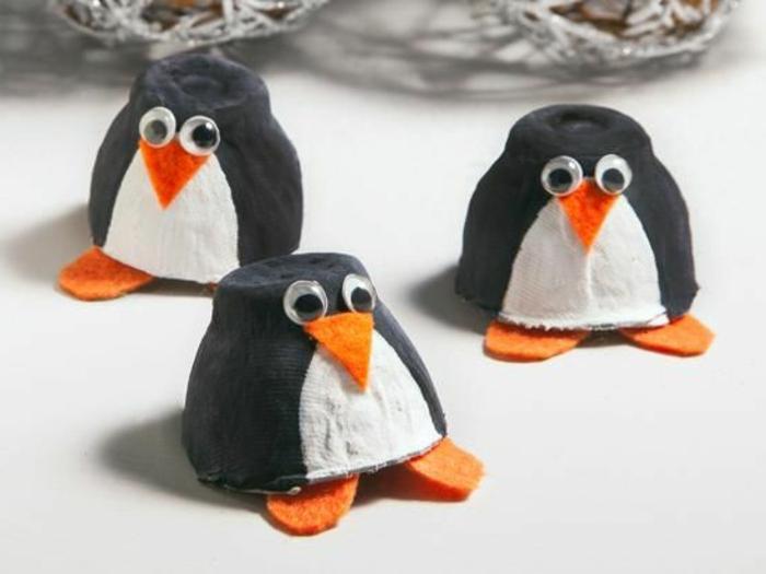 bricolage boite a oeuf, trois pingouins avec des becs, des pieds et des yeux