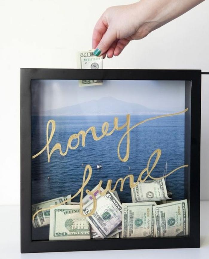 cadre en bois et verre, billets de banques pour faire un voyage de noces, une photo de paysage bord de mer pour faire rever, tirelire originale