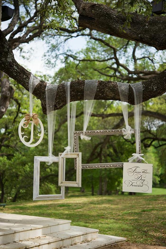 des cadres suspendus à une branche d'arbre, idée photobooth facile à réaliser