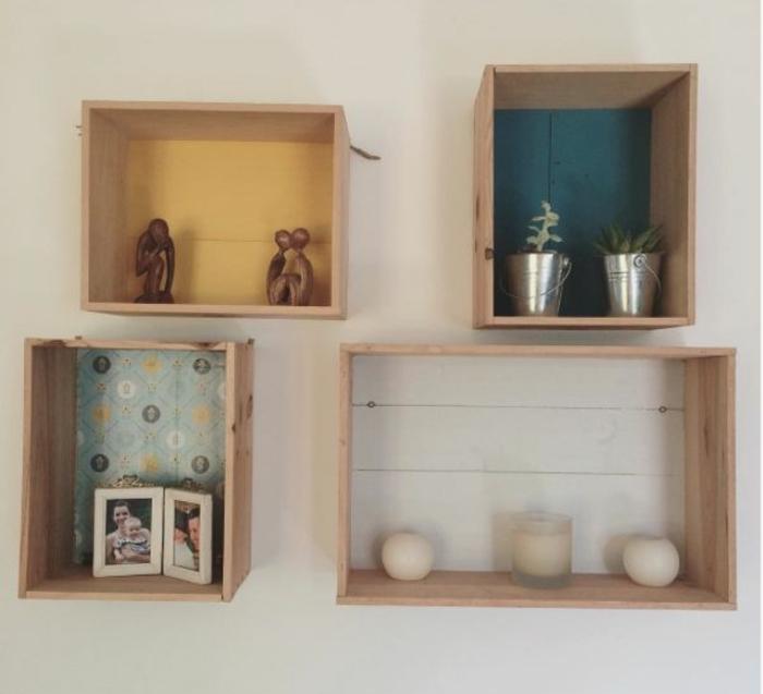 meuble en cagete, étagères murales caisses fonds customisés à l aide de papier coloré, bougies, pots de fleurs, petites sculptures en bois, photos de famille