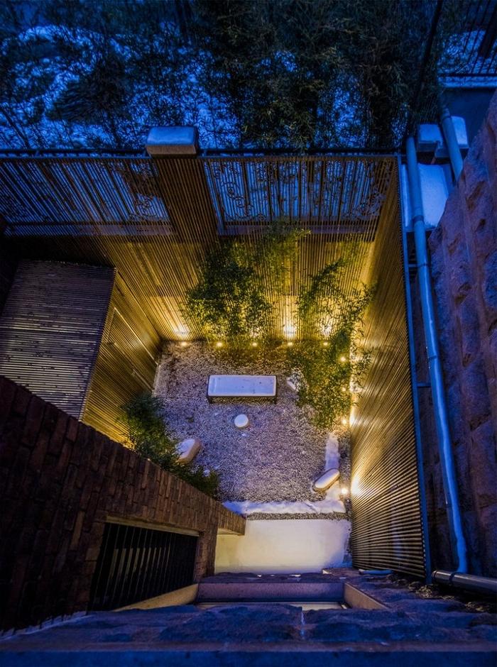 déco de jardin zen, clôture en bois, terrain avec galets, éclairage extérieur, plantes rampantes