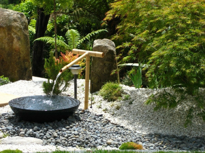 parterre de fleurs avec galets, fontaine zen en bambou, arbres verts, rochers dans le jardin