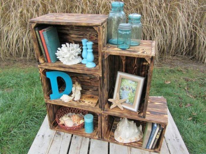 étagère en cagette, plusieurs caisses structure asymetrique, rangement livres, chandeliers, bocaux en verre, etoile de mer, escargots de mer noire, lettre en bois repeinte en bleue