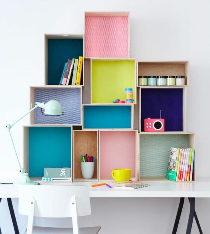 étagère cagette murale constituée de caisses en bois clair de tailles différentes. fond customisé avec du papier coloré, rangement livres et fournitures de bureau, bureau et chaise blancs