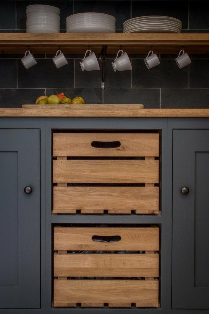cagette en bois intégrée au meuble cuisine, facade cuisine gris anthracite, carrelage gris, vaisselle blanche, fruits,