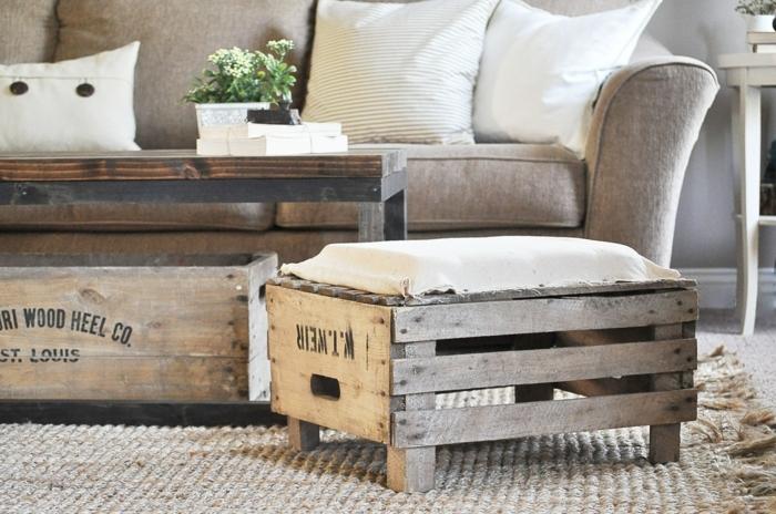 canapé gris, tapis gris clair, table basse en bois et métal, coussins gris et blanc, tabouret en cagette bois