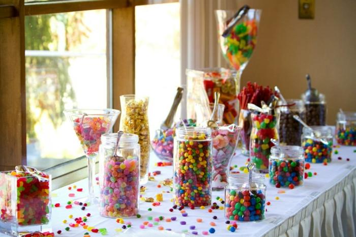 decoration bar a bonbon mutlicolore, dragées et boules de gomme rangée dans des récipients en verre, bocaux et verres, bonbons dispersés sur la table