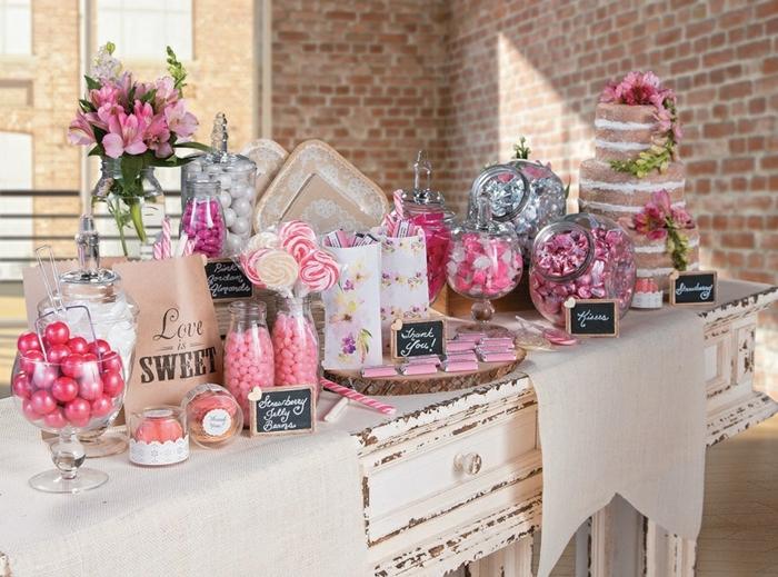 candy bar mariage vintage en rose et blanc, sucettes, caramels, petits chocolats, dragées, fleurs rose, table vintage, gateau a etages gourmand