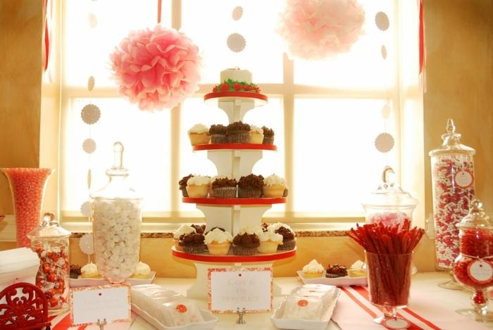 dragées, boules de gomme. cupcakes, bonbons lindor, decoration bar a bonbon en rouge, blanc et rose, fleurs en papier de soie rose